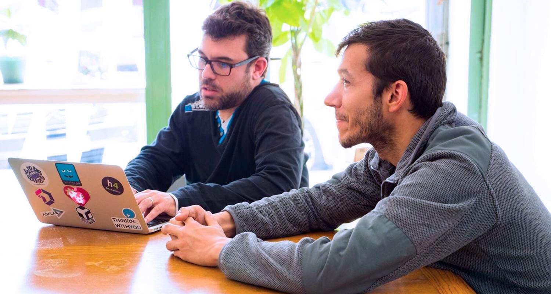 Dos autónomos de la empresa Thinking With You están trabajando en Freeland Coworking, reunidos en una mesa.