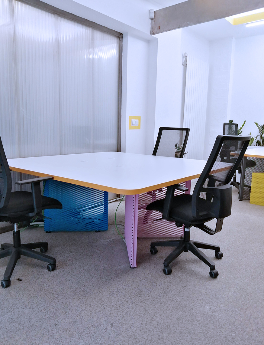 Despacho privado en en el espacio coworking Freeland en Madrid, donde sale una mesa para tres personas, con patas de colores, diseñado por Freeland.