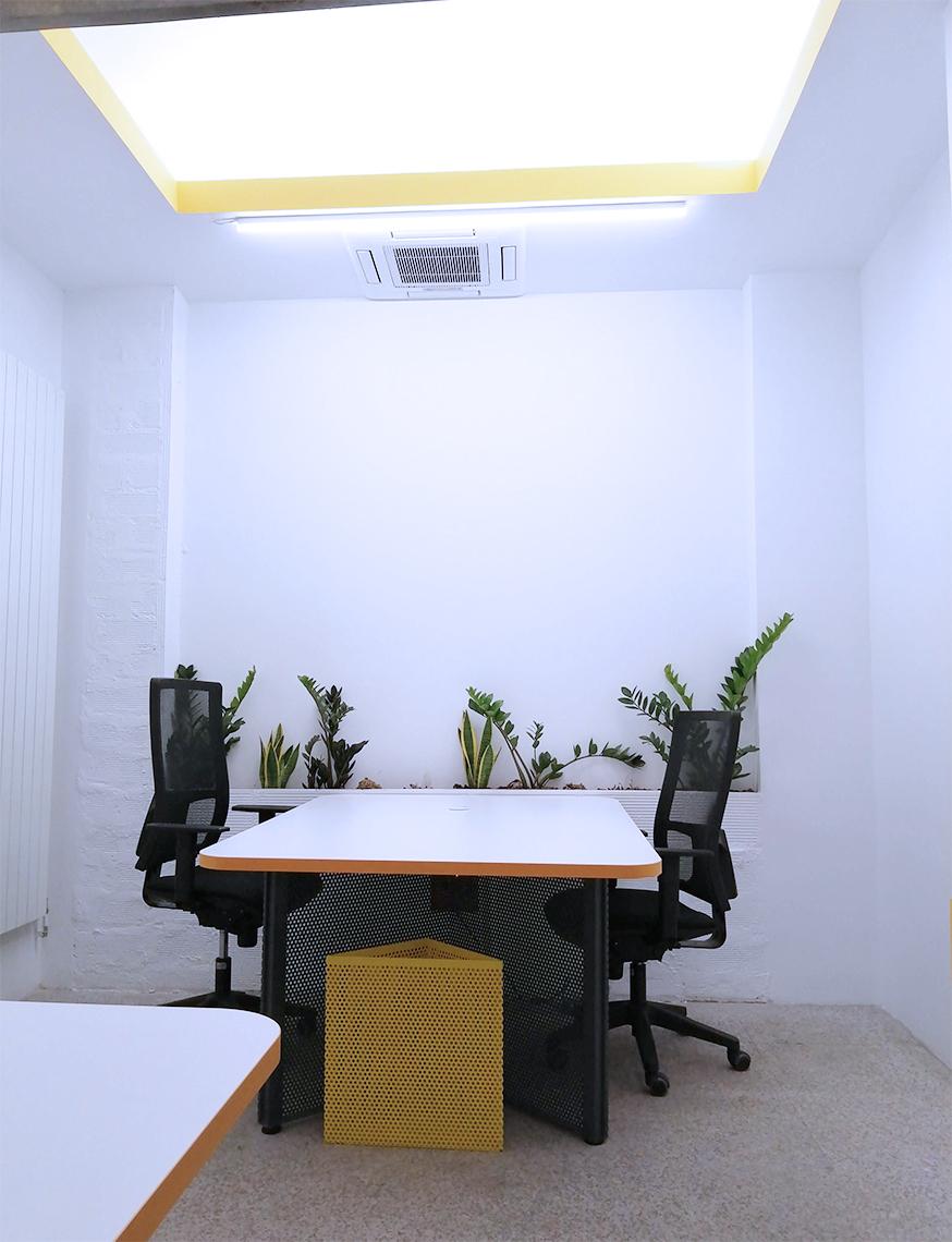 Suite o despacho privado en el espacio de coworking Freeland en Madrid, en el barrio de Adelfas, distrito Retiro, donde sale una mesa para dos personas, con una pata de color gris y una papelera de color amarillo y una jardinera de fondo.