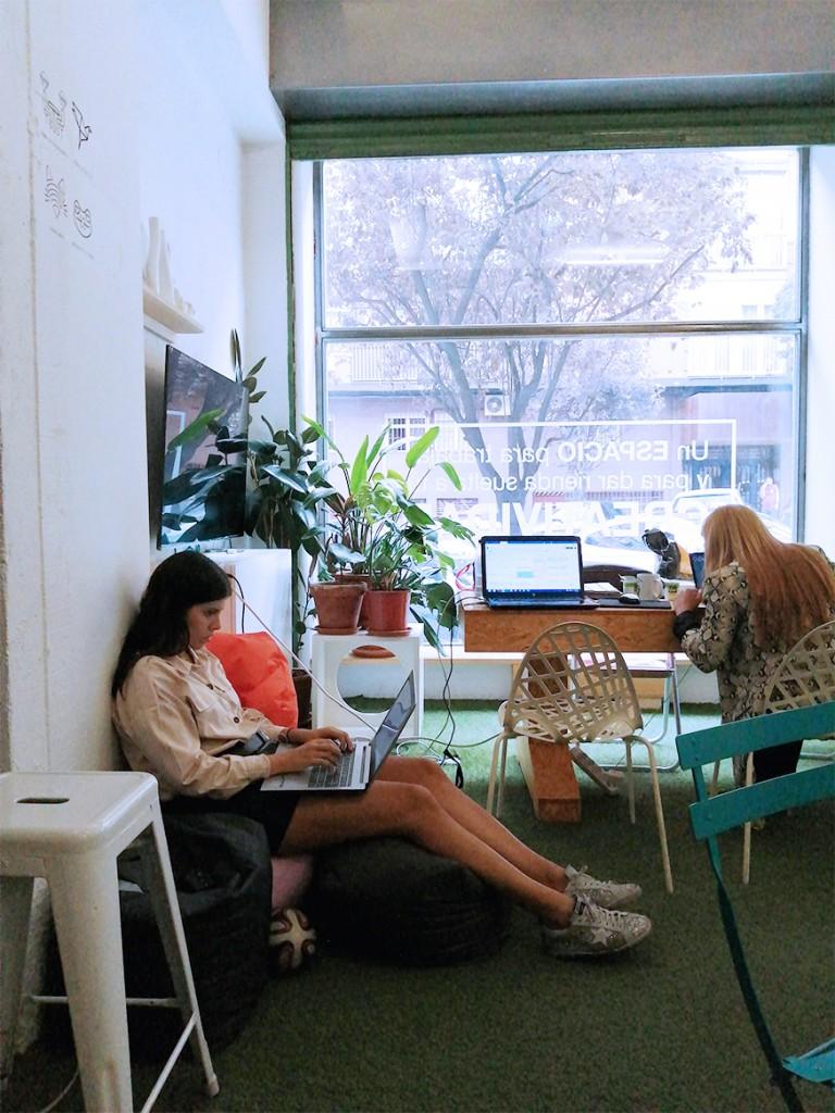 Dos emprendedoras salen cómodamente trabajando en el espacio de coworking Freeland, en Madrid, una de ellas con el ordenador en las rodillas, la otra en una mesa. Rodeadas por mobiliario colorido y plantas.
