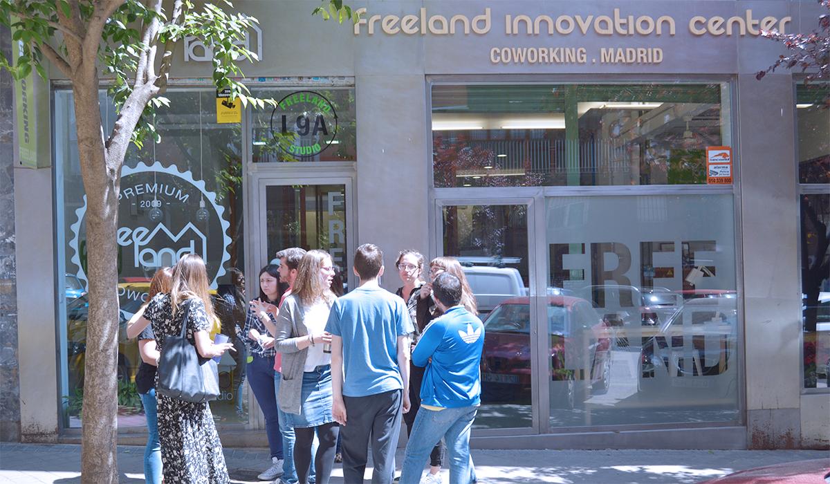 Espacio Coworking Freeland en Madrid, un grupo de freelance están de pie frente a la puerta principal de.