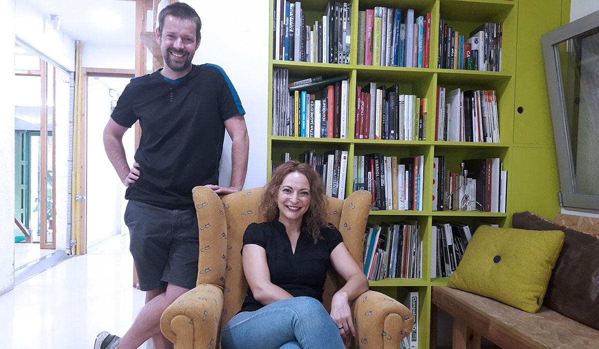 Dos freelance, Teun y Aurea, uno sentado y otro de pie junto a una estantería en Freeland Coworking