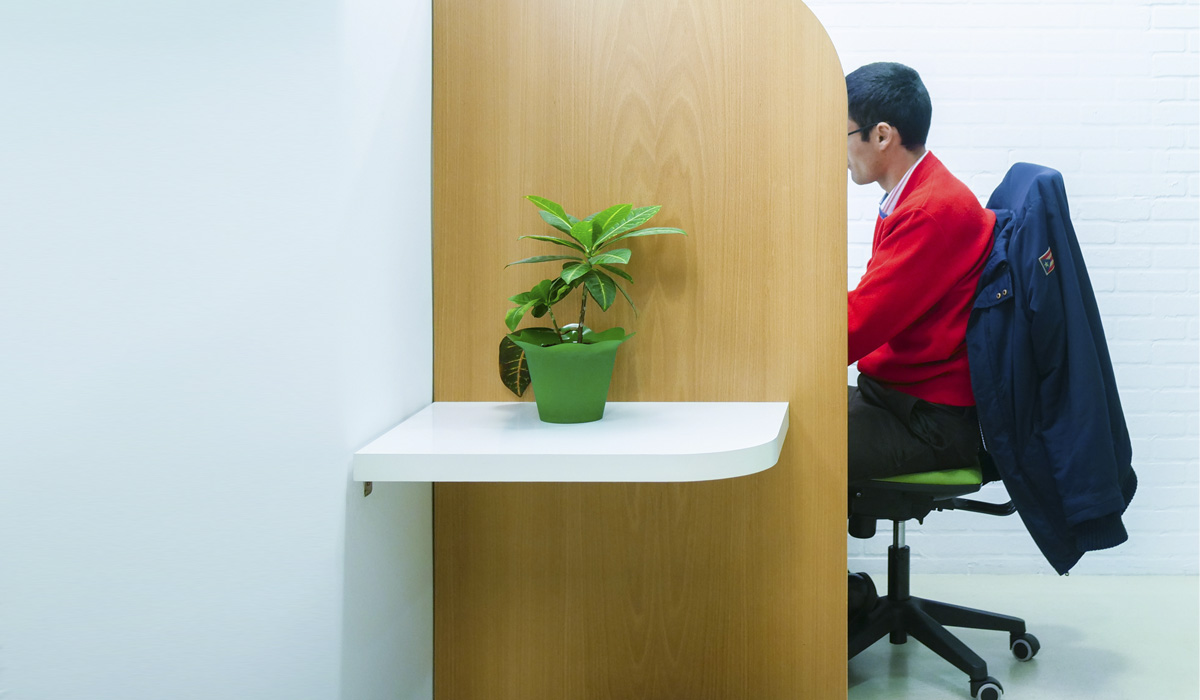 hombre sentado con higiene postural yergonomía en la oficina o coworkingl frente coworking trabajando