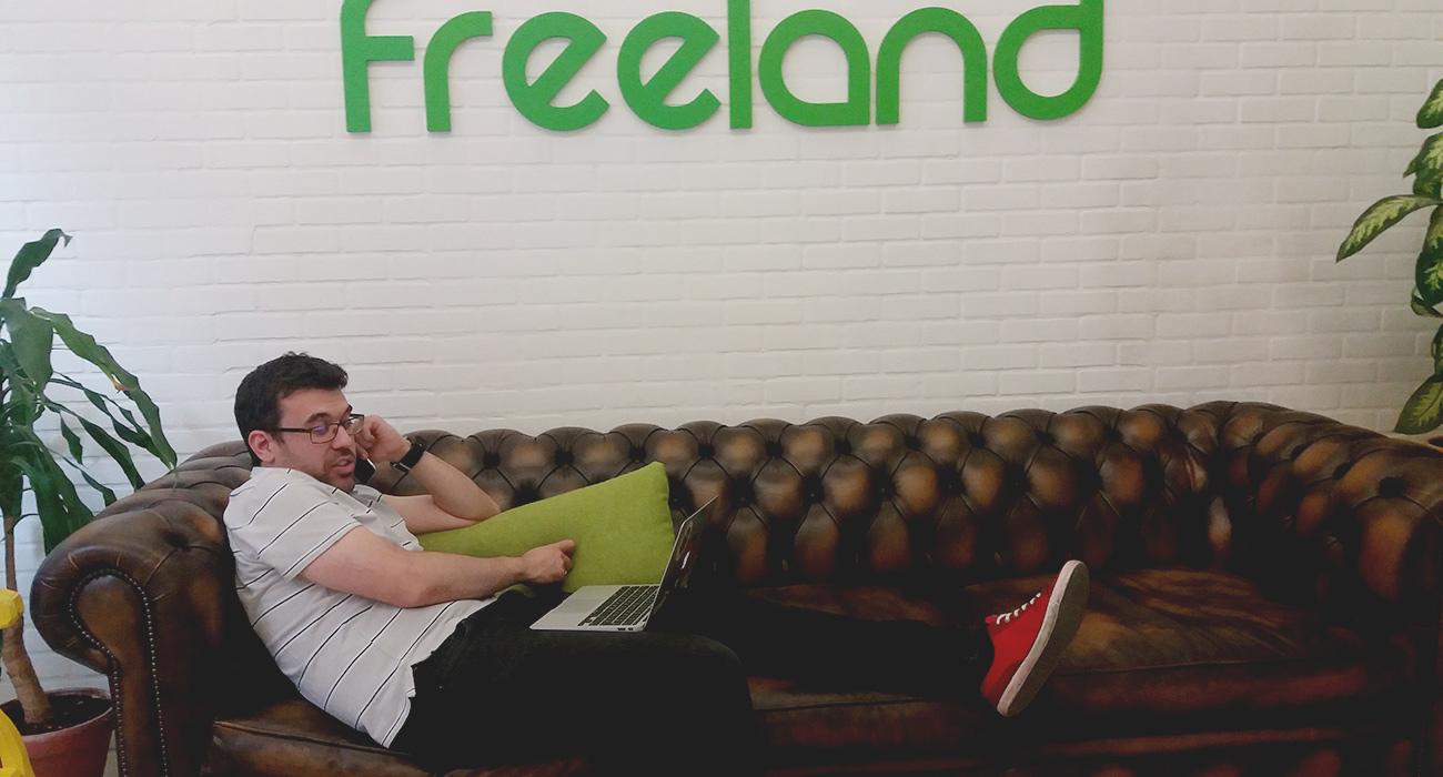 Freelance hablando por teléfono en un sillón de cuero en la entrada de Freeland