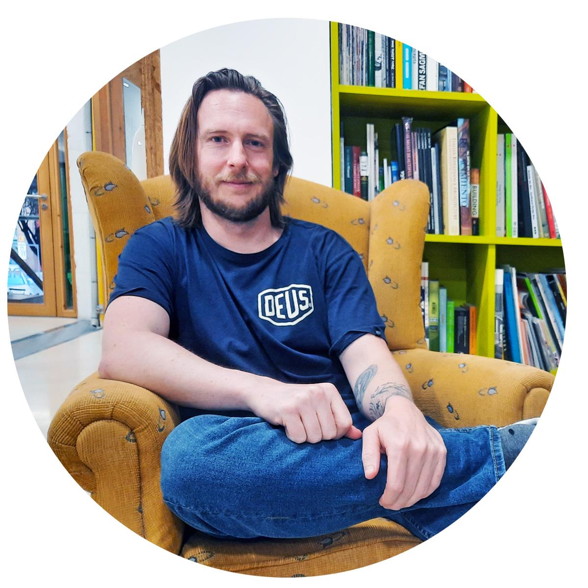Mike Keene nos cuenta cómo ser productivo con un trabajo flexible sentado en una butaca sujetándose una pierna con una estantería de fondo de color verde en Freeland Coworking