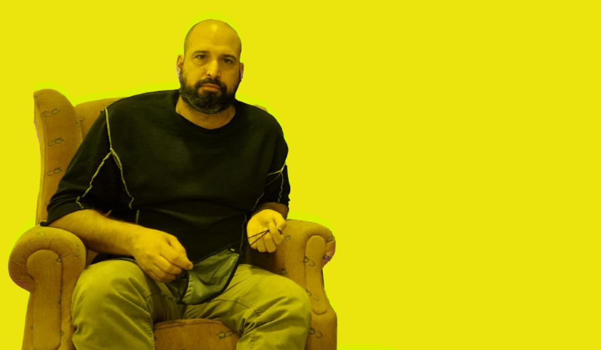 Carlos Garcia sentado en un sillón en Freeland con fondo amarillo